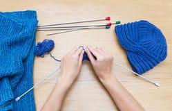 Tricotage à la main avec des aiguilles de tricotage Une femme tricote à un t en bois Images stock