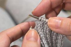 Tricotage avec des aiguilles de tricotage dans des mains femelles Image libre de droits