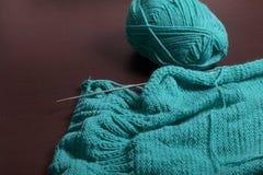 Tricotage avec des aiguilles de tricotage Sur la surface foncée des mensonges de table un produit tricoté non fini avec des aigui Photo stock