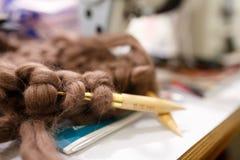 Tricotage avec le fil brun mou épais de couleur de laine sur les aiguilles Images stock