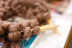 Tricotage avec le fil brun mou épais de couleur de laine sur les aiguilles Image stock