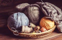 Tricotage, ciseaux d'embrouillements et bobines dans un panier Image stock