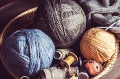 Tricotage, ciseaux d'embrouillements et bobines dans un panier Photo libre de droits