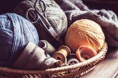 Tricotage, ciseaux d'embrouillements et bobines dans un panier Photographie stock libre de droits