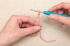 Tricotage d'un brin de fil orange avec le crochet de crochet Image libre de droits