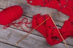 Tricotage de rouge et aiguilles de tricotage en bois Photographie stock