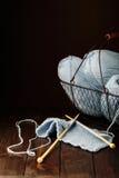 Tricotage du fil bleu-clair sur le fond en bois de brun foncé Photographie stock