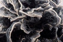 tricotage L'écharpe noire et blanche ondulée s'est située dans le tas Photo stock