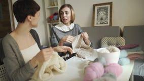 Tricoteiro de duas mulheres que fala e que sorri no estúdio da costura Lãs de confecção de malhas da mulher vídeos de arquivo