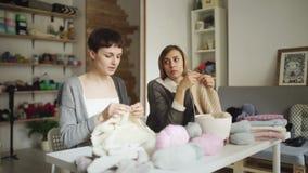 Tricoteuse de deux femmes faisant le tissu de laine se reposant à la table dans l'atelier de textile banque de vidéos