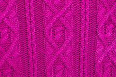 Tricotez la texture du tissu tricoté par laine de rose avec le modèle de câble comme fond Texture magenta photo stock