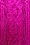 Tricotez la texture du tissu tricoté par laine de rose avec le modèle de câble comme fond Texture magenta photo libre de droits