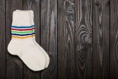 Tricotez les chaussettes blanches de laine sur le fond en bois foncé Photographie stock libre de droits