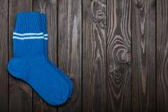 Tricotez les chaussettes bleues de laine sur le fond en bois foncé Photos stock