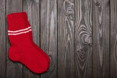 Tricotez les chaussettes rouges de laine sur le fond en bois foncé Images libres de droits