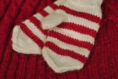 tricotez Mitaines rayées tricotées faites maison sur le fond tricoté de modèle images stock