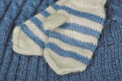 tricotez Mitaines rayées tricotées faites maison sur le fond tricoté de modèle photo stock