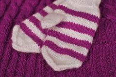 tricotez Mitaines rayées tricotées faites maison sur le fond tricoté de modèle photographie stock libre de droits