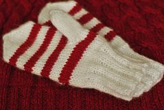 tricotez Mitaines rayées tricotées faites maison sur le fond tricoté de modèle photos libres de droits