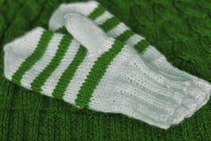 tricotez Mitaines rayées tricotées faites maison sur le fond tricoté de modèle image libre de droits