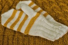 tricotez Mitaines rayées tricotées faites maison sur le fond tricoté de modèle image stock
