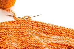 Tricottando, lana arancio su bianco Immagini Stock
