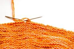 Tricottando, lana arancio su bianco Immagine Stock