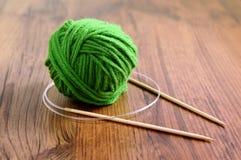 Tricotti gli aghi e la lana sulla tavola Immagini Stock