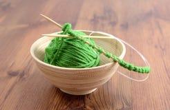 Tricotti gli aghi e la lana sulla tavola Fotografie Stock Libere da Diritti