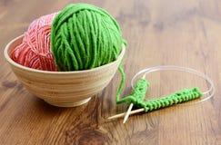 Tricotti gli aghi e la lana sulla tavola Fotografia Stock