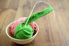 Tricotti gli aghi e la lana sulla tavola Fotografia Stock Libera da Diritti
