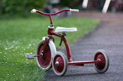 Tricycle. A red child tricycle in a garden Royalty Free Stock Images