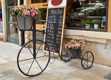 Tricycle antique et fleurs artificielles Photo stock