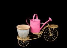 Tricycle avec le pot d'arrosage rose sur le backg noir supérieur photographie stock libre de droits
