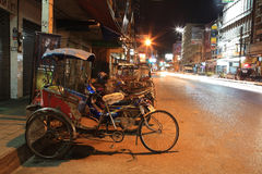 Tricycle bicycle parks on the urban street at nigh Royalty Free Stock Photography