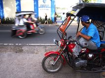 Tricycle driver patiently waits at a sidewalk for passengers. ANTIPOLO CITY, PHILIPPINES - SEPTEMBER 26, 2016: A tricycle driver patiently waits at a sidewalk royalty free stock image