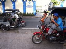Tricycle driver patiently waits at a sidewalk for passengers. ANTIPOLO CITY, PHILIPPINES - SEPTEMBER 26, 2016: A tricycle driver patiently waits at a sidewalk royalty free stock images