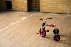 Tricycle in empty gym. Old tricycle in and empty lonely old gym Royalty Free Stock Photography