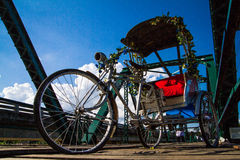 Tricycle garé sur le pont en bois Photographie stock