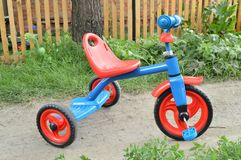 Tricycle kids bike Bicycle blue and red new is on the road in the garden to entertain children.  stock photography
