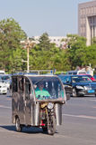 Tricycle motor taxi in busy traffic, Beijing, China. BEIJING-MAY 29, 2013. Tricycle motor taxi downtown. This small taxi is similar to Thailand Tuk Tuks Royalty Free Stock Photo