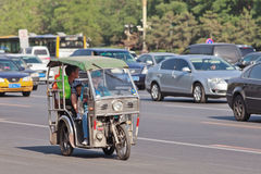 Tricycle motor taxi in busy traffic, Beijing, China. BEIJING-MAY 29, 2013. Tricycle motor taxi downtown. This small taxi is similar to Thailand Tuk Tuks Royalty Free Stock Image