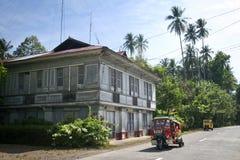 Tricycle passant la Chambre traditionnelle de Filipno sur l'île de Camuigan, M Images stock