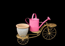 Tricycle with pink watering pot on top black backg Royalty Free Stock Photography