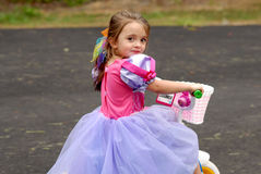 Tricycle Princess. A pretty young girl dressed in her princess dress with a sweet smile on her face riding her tricycle Royalty Free Stock Photography