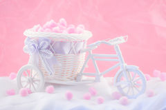 Tricycle souvenir on a pink background with fluffy donuts.  stock photography