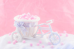 Tricycle souvenir on a pink background with fluffy donuts.  stock photo