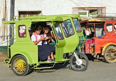 Tricycles with two students using mobile phones, Philippines stock images