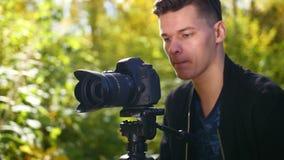 4 TRIEB, ein Mann mit Lächeln einer Kamera an der Kamera, macht Fotos auf einem Stativ in einem Forest Park stock video footage