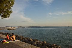 Summer in Trieste, Italy. Trieste, Barcola sea promenade at sunset, couple enjoy the summer warm weather Stock Photo
